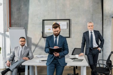 three professional bearded businessmen in suits and eyeglasses working together in office