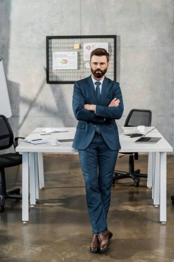 Full length view of confident bearded businessman in suit and eyeglasses standing with crossed arms in office stock vector