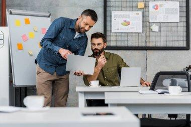 dizüstü bilgisayarlar kullanarak ve office projesinde tartışırken iş adamları