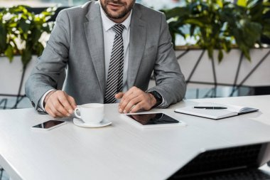 cropped image of businessman taking cup of coffee at table in office