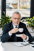 Photo handsome middle aged businessman holding cup and plate and looking at camera in office