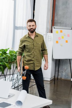 handsome bearded businessman standing with longboard and looking at camera in office