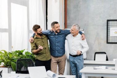three smiling handsome businessmen hugging and standing in office