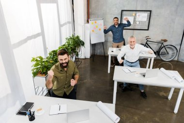 high angle view of excited handsome businessmen showing yes gesture in office