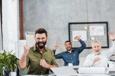 happy handsome businessmen showing yes gesture in office