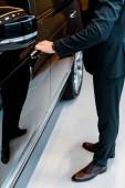 Oříznout obrázek podnikatel v obleku otevírání dveří černé automobilu