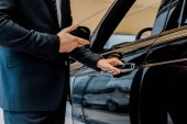 oříznutý obraz mužské autosalon otevřel dveře a ukázal na černé automobil v autosalonu