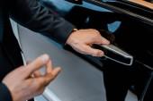 částečný pohled mužského autosalon otevřel dveře a ukázal na černé automobil v autosalonu