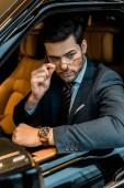 Stylový podnikatel s luxusní hodinky nasadil brýle, zatímco sedí v autě