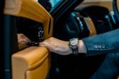 Oříznout obrázek podnikatel s luxusní hodinky zavírání dveří, zatímco sedí v autě