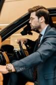 Fotografie Seitenansicht der Geschäftsmann mit Luxusuhr Tür beim Sitzen im Auto