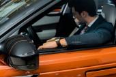 selective focus of stylish businessman sitting in luxury orange car