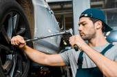 Photo focused male auto mechanic in working overall working with wheel wrench at auto mechanic shop