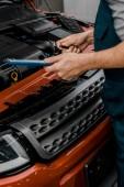 částečný pohled opravář s Poznámkový blok vyšetřující auto v auto-servis
