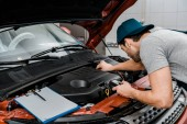 Photo auto mechanic with multimeter voltmeter checking car battery voltage at mechanic shop