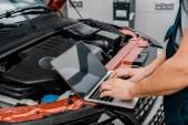oříznutý snímek auto mechanik, pracují na notebooku s prázdnou obrazovkou v automobilu s otevřené auto kryt na mechanik shop