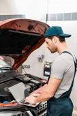 Fotografie boční pohled na auto mechanik pracovat na notebooku v automobilu s otevřené auto kryt na mechanik shop