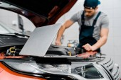 Photo selective focus of laptop and auto mechanic at auto repair shop