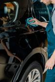 Fotografie částečný pohled auto mechanik čisticí vůz s hadr na auto-servis
