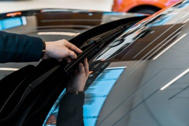 partial view of businessman adjusting windshield wipers of black automobile