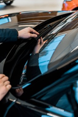 cropped image of businessman adjusting windshield wipers of black automobile