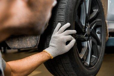 Cropped shot of repairman in protective glove examining car wheel at auto repair shop stock vector