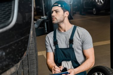 young repairman with notepad checking car wheels at auto repair shop