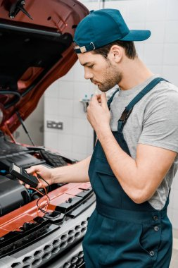 side view of auto mechanic with multimeter voltmeter checking car battery voltage at mechanic shop