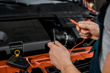 cropped shot of auto mechanic with multimeter voltmeter checking car battery voltage at mechanic shop