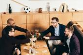 Fotografie vysoký úhel pohledu mnohonárodnostní obchodních týmu cinkání, pije, zatímco odpočívá společně v kavárně