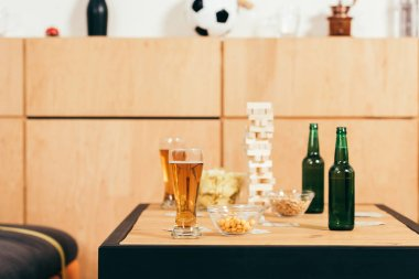 close up view of beer, snacks and blocks wood game on tabletop in cafe