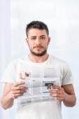 pohledný muž drží noviny a ráno doma při pohledu na fotoaparát