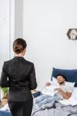 přítelkyně v obleku a přítel v pyžamu, čtení novin v ložnici ráno, koncept rovnosti pohlaví
