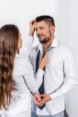 přítelkyně vázání přítele kravatu a dotýká vlasy ráno ve všední den v pojetí ložnice, sociální role