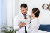 přítelkyně vázaný přítele kravatu a on pomocí tabletu ráno doma, koncept sociální role