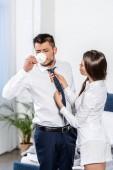 přítelkyně vázaný přítel kravatu, zatímco on pít kávu ráno doma, koncept sociální role