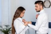 Boční pohled přítelkyně zapínání manžety přítel ráno doma, sexismus koncepce