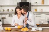 přítel, líbat přítelkyně, zatímco ona řezání pomeranče v ráno v kuchyni, koncept genderové stereotypy