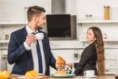 přítel má snídaně a přítelkyně uvedení konvici na kamnech doma, sexismus koncepce
