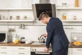 pohledný muž v obleku uvedení konvici na vařič ráno v kuchyni