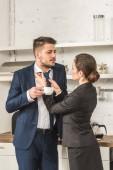 přítel drží šálek kávy a přítelkyně vázání jeho kravatu doma, koncept sociální role