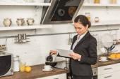 atraktivní žena nalijete kávu do šálku a při pohledu na tabletu ráno v kuchyni