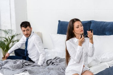 Boyfriend looking at girlfriend applying lipstick in bedroom in morning stock vector