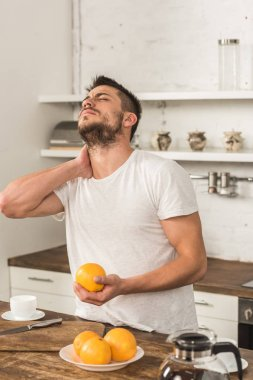 Handsome man holding orange and touching neck in morning at kitchen stock vector