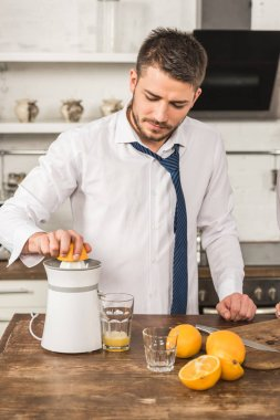 handsome man making orange juice with squeezer in morning at kitchen