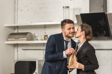 girlfriend giving lunch to boyfriend and kissing him in morning at kitchen, social roles concept