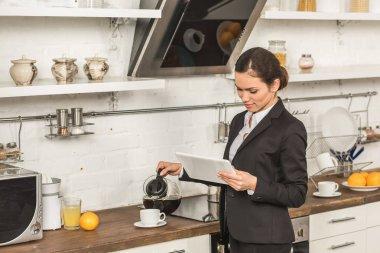 çekici kadın kahve Kupası ve tablet vasıl sabah mutfağa seyir içine dökme