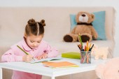 Fotografie adorable focused child writing with pencil and studying at home