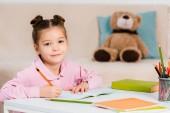 roztomilé dítě psaní tužkou a usmívá se na kameru při studiu doma