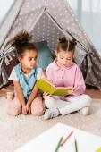 entzückende multiethnischen Kinder sitzen auf Teppich und Buch zusammen